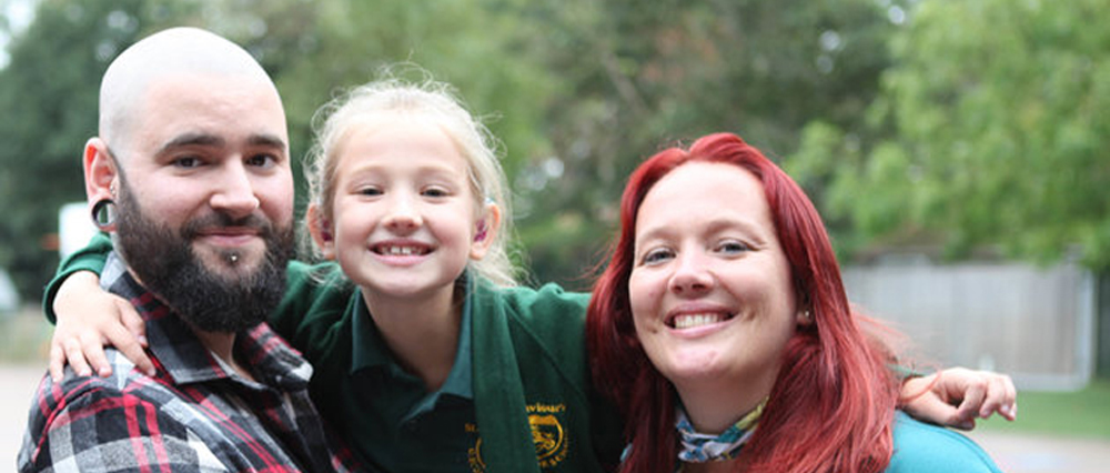 All smiles: Livi with her parents, Aaron and Sally before her implant operation